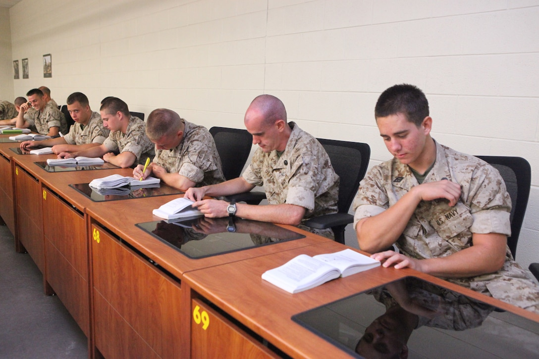 Sailors enrolled in the Chaplain and Religious Program Specialist Expeditionary Skills Training course study Marine Corps knowledge books during a common skills class aboard Camp Johnson, recently.  The eight-week course hones the sailors' combat skills and immerses them in the Marine Corps lifestyle so they will be better prepared to protect their chaplains, Marines and fellow sailors in combat.
