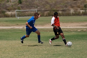 Randolph Air Force Base soccer team plays other intramural teams from other Air Force bases from across the United States. The games were part of 2010 Defender's Cup held at the South Texas Area Regional Soccer Complex in San Antonio, Texas.  Randolph's Kevin Meyers chases a Cannon AFB player. Randolph beat Cannon 2-0. (U.S. Air Force Photo/Brian McGloin)