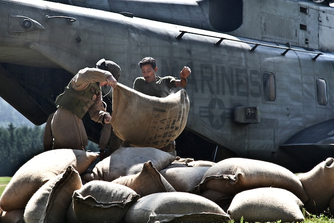 u s department of > photos > photo essays > essay view a u s navy crew member and a i ier unload food to be given to flood