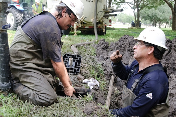 Mark Rangel and Andy Montemayor, 902nd Civil Engineering Squadron, coordinate their efforts to replace a the broken pipe of a water main caused by ground shifting as a result of Tropical Storm Hermine. (U.S. Air Force photo/Steve Thurow)