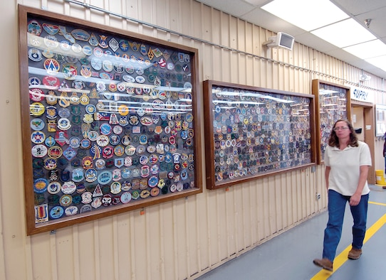 Fabric and Life Support Unit Chief Ann Jones passes hundreds of patches proudly displayed along a shop wall.  They come from every branch of service and squadrons all over the world who have used the unit's services. (Air Force photo by Margo Wright)