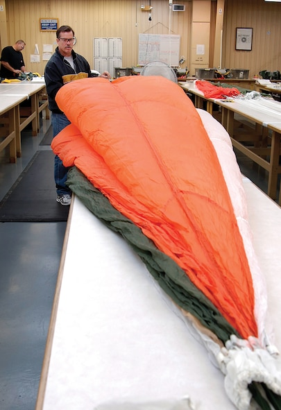 """David Weiss packs a 28-foot long B-1B spare personnel parachute.  Chutes are inspected and repacked every four months in the Fabric and Life Support Unit. """"We hope what we do is the biggest waste of time,"""" says unit chief Ann Jones. """"Our goal is for our gear to never be used. But if they need it, it's done right."""" (Air Force photo by Margo Wright)"""