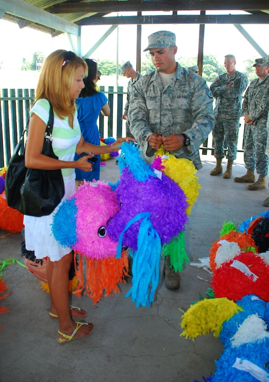 SOTO CANO AIR BASE, Honduras --  Yajaira Matute, a local school teacher, receives piñatas from Staff Sgt. Josue Santiago, of Army Forces, here Sept. 8. Sergeant Santiago and other Joint Task Force-Bravo volunteers filled the piñatas with candy and other treats and delivered them to local school representatives in celebration of Honduras' Children's Day, which takes place Sept. 10. (U.S. Air Force photo/Martin Chahin)