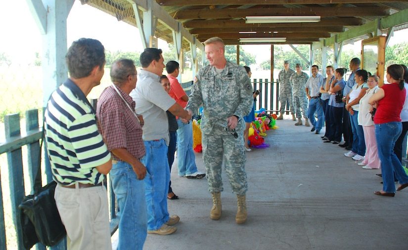 SOTO CANO AIR BASE, Honduras --  Col. Gregory Reilly, the Joint Task Force-Bravo commander, greets representatives from local schools Sept. 8 as they come to pick up piñatas donated by Team Bravo. Civil Affairs here purchased the piñatas and JTF-Bravo volunteers filled them with candy and other treats in celebration of Honduras' Children's Day, which takes place Sept. 10. (U.S. Air Force photo/Martin Chahin)