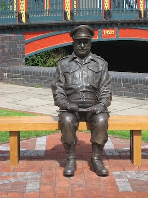 """This bronze statue of Capt Mainwaring is situated close to the bridge which crosses the River Little Ouse in the centre of Thetford, Norfolk. Captain Mainwaring was the commander of the fictional World War II Home Guard unit featured in the British sitcom, """"Dad's Army"""". Much of the series was filmed in East Anglia.The statue shows Mainwaring wearing his Home Guard uniform, seated on bench, with his baton across his knees. (U.S. Air Force photo by Suzanne Harper)"""