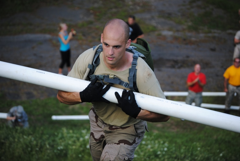 Staff Sgt. Dedrick Baublitz from the 103rd Security Forces Squadron cradles a water-filled PVC pipe up a hill as a member of the Connecticut Air National Guard Emergency Service Team during the Connecticut SWAT Challenge physical fitness test in West Hartford, Aug. 26, 2010. The Guard team took 20th place overall and 10th place in the physical fitness challenge. (Photo courtesy of Ms. Denise Davis)
