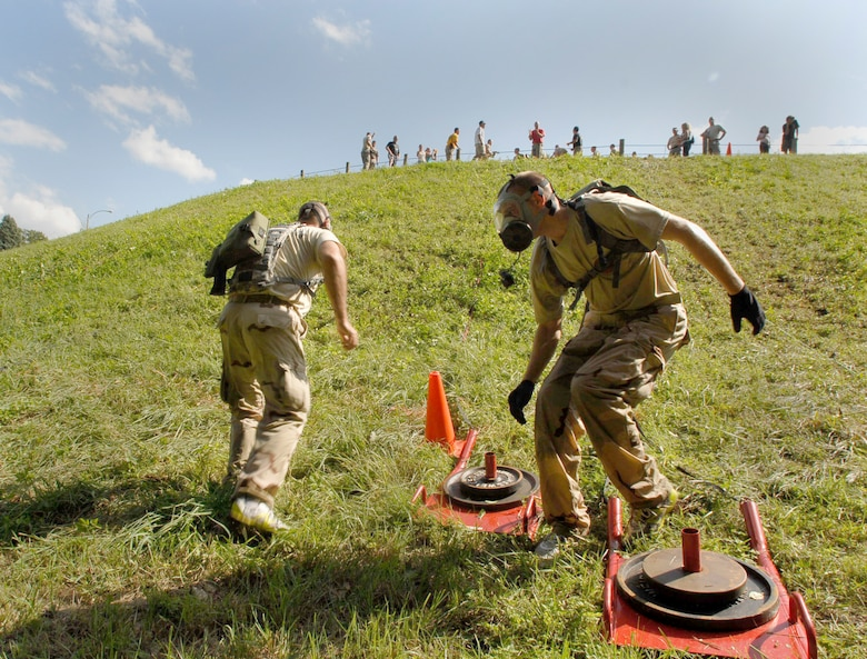 Two 103rd Security Forces Squadron personnel turn to charge back up a hill in gas masks after pulling a weighted sled during the physical fitness challenge at the Connecticut SWAT Challenge Aug. 26, 2010. The PT course this year was held at the West Hartford Reservoir and covered 4.7 miles consisting of 32 distinct obstacles. (U.S. Air Force photo by Tech. Sgt. Josh Mead)