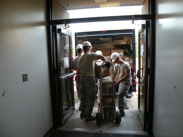 Members of the 103rd  Air and Space Operations Group work together at Bradley Air National Guard Base, East Granby, Conn. with the 118th Airlift Squadron's Life Support section Aug. 26, 2010, to move equipment and other gear in preparation for construction efforts. (U.S. Air Force photo by Staff Sgt. Hope Morris)