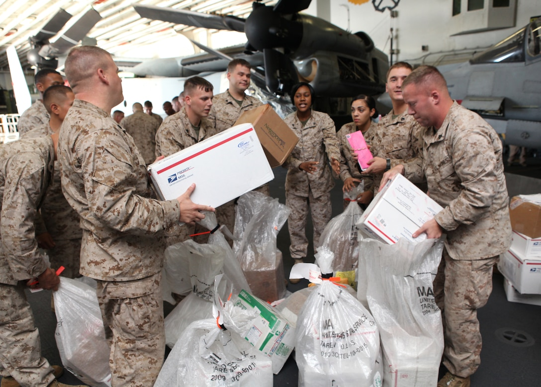 Command Element Marines with 26th Marine Expeditionary Unit organize and separate mail in the hangar bay during their first mail call aboard USS Kearsarge in the Mediterranean Sea, Sept. 12, 2010.  Care packages and hand-written mail are a big part of increasing moral and just one way for family and friends to stay in touch with deployed Marines.