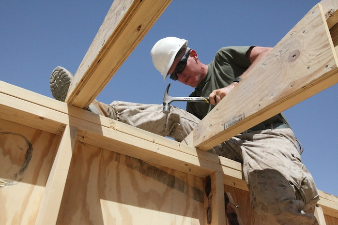 Lance Cpl. Dwason E. Griffith, a combat engineer with Alpha Company, 9th Engineer Support Battalion, 1st Marine Logistics Group (Forward), nails an A-frame to a wall, Sept. 12. Since their arrival on the FOB, Sept. 2, engineers from 9th ESB have been building structures to improve living conditions and security.