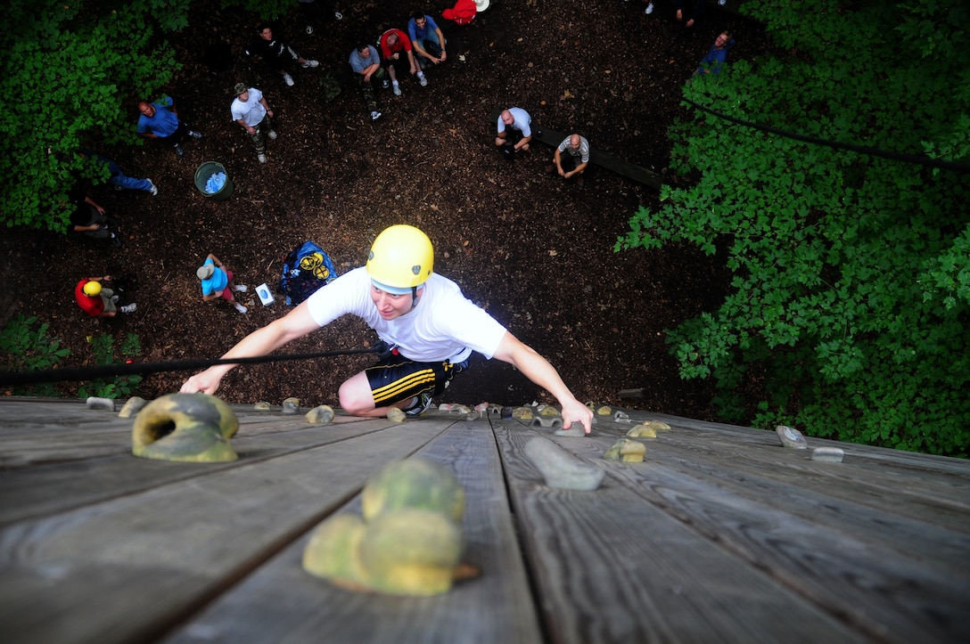 WALL CLIMB  U.S. Air Force Tech. Sgt. Travis Kowalski navigates the wall climb at the Pretty Lake Adventure Center, Kalamazoo, Mich. Aug. 21, 2010 while 110th Airlift Wing Service members watch from below. The 110th Airlift Wing servicemembers were participating in the Adventure Centers' Leadership training course. (U.S. Air Force photo by Tech. Sgt. Sonia Calbaugh/Released)