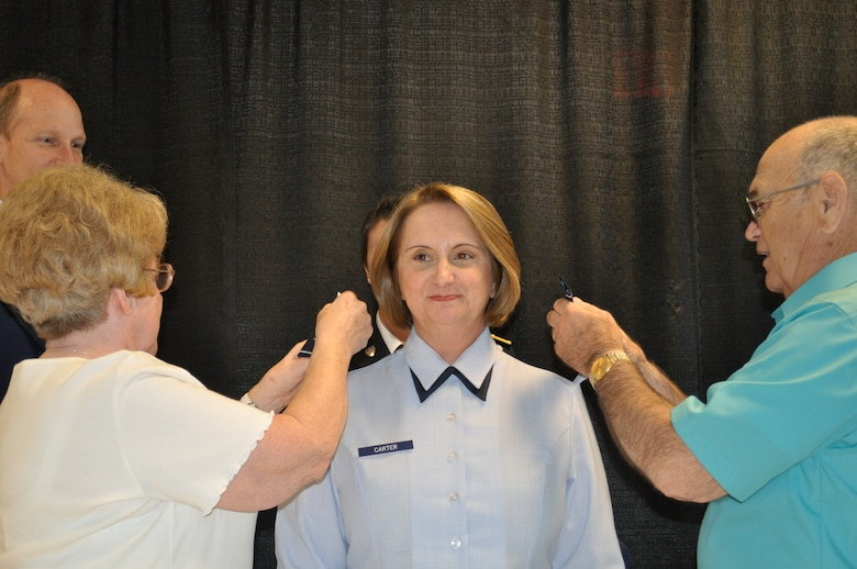 Carter's father Gene Gelinas, and his wife Helen replace colonel epaulets with brigadier general epaulets during her promotion ceremony May 28.