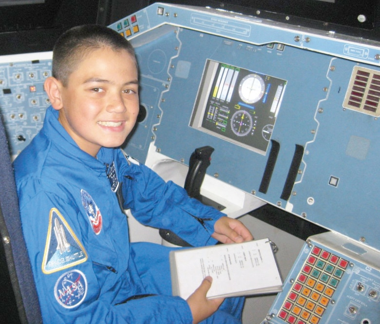 Charles Macleod reviews a checklist in the space shuttle simulator in Huntsville, Ala. Charles is a 9th grader from Redlands, Calif., who was selected to attend Air Force Space Camp this year.  (U.S. Air Force photo courtesy of Charles Macleod)