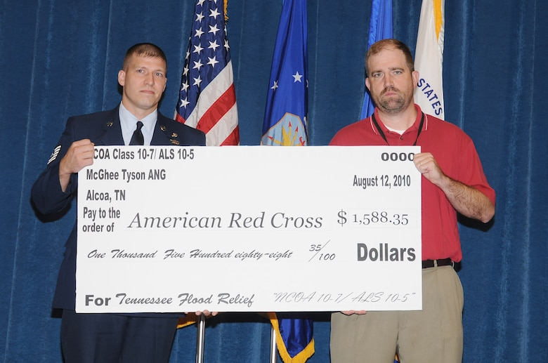 McGHEE TYSON AIR NATIONAL GUARD BASE, Tenn. - NCO Academy student, Tech. Sgt. Shane A. Merillat, left, a paralegal at Wright-Patterson AFB, Ohio, presents a check for $1,588.35 to Chris Davis, executive director for the American Red Cross, Blount County Chapter, during the combined graduation ceremony of NCO Academy Class 10-7 and Airman Leadership School Class 10-5 on the campus of The I.G. Brown Air National Guard Training and Education Center here, Aug. 12, 2010. (U.S. Air Force photo by Master Sgt. Kurt Skoglund/Released)