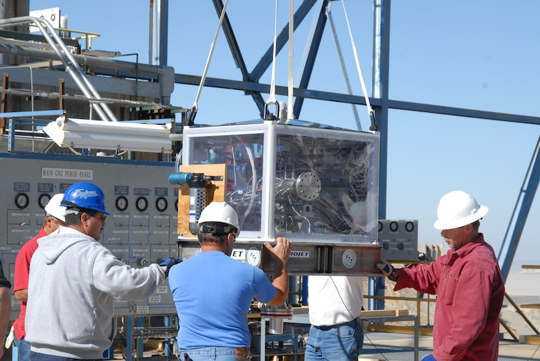 Air Force Research Laboratory workers use a crane to remove a newly delivered Upper Stage Engine Technology turbo pump from its shipping crate.  The USET turbo pump will be connected to AFRL's 2A rocket test stand where it will undergo a series of tests using liquid hydrogen.  (Air Force photo by Kenji Thuloweit)