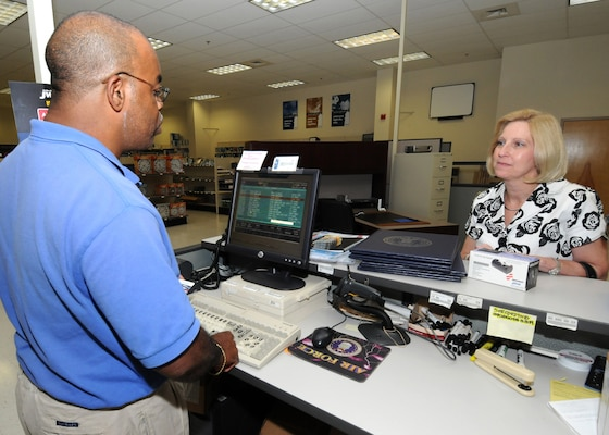 Willie Wilson, a cashier at the Randolph Base Service Center, assists customer Fran Ryan, a workflow manager with A4/7.  Mr. Wilson has problems reading small text, so a computer program for the visually impaired enlarges text on his computer screen.(U.S. Air Force photo/David Terry)