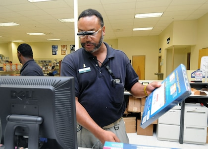 A monocular attached to his glasses allows cashier John Woolridge to read small text at the Randolph Base Service Center. The optical device and a special program which enlarges text on the computer screen has enabled Mr. Woolridge to perform his duties. (U.S. Air Force photo/David Terry)