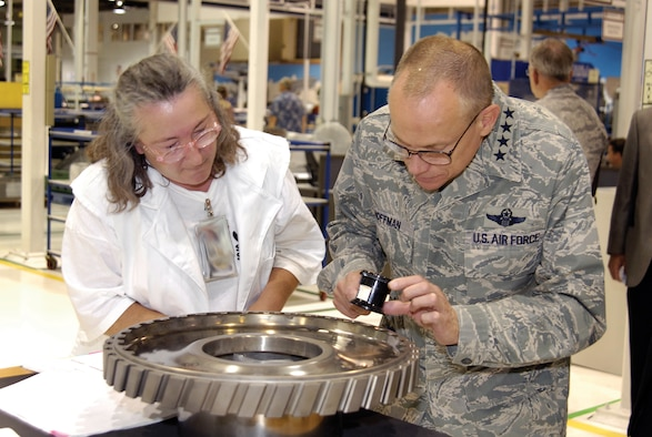 Tinker machinist Debbie Medina shows Gen. Donald Hoffman, commander of Air Force Materiel Command, a nick she discovered in an F100 third-stage disk during a visual inspection. The AFMC commander came to Tinker Sept. 9 and 10 to visit shops across base. Ms. Medina is with the 76th Propulsion Maintenance Squadron and works in Bldg. 3001. (U.S. Air Force photo/Margo Wright)