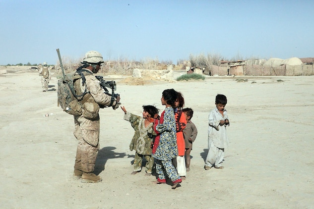 Lance Cpl. Demeterius Duncan, a mortarman with Weapons Platoon, Company B, 1st Light Armored Reconnaissance Battalion, passes out candy to the local children during a patrol at Shabu, Afghanistan, Sept. 15. The Marines with the cooperation of the locals have found the largest drug cache in their area with approximately 60 kilos of processed drugs.