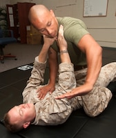 Sgt. Kevin A. Aguilar, dispatching and licensing noncommissioned officer in charge for Headquarters and Service Battalion, U.S. Marine Corps Forces, Pacific, demonstrates how to perform an arm bar from the mount while performing his duties as a Marine Corps Martial Arts Program instructor. Aguilar also serves as a suicide prevention instructor trainer and Mentors in Violence Prevention instructor.