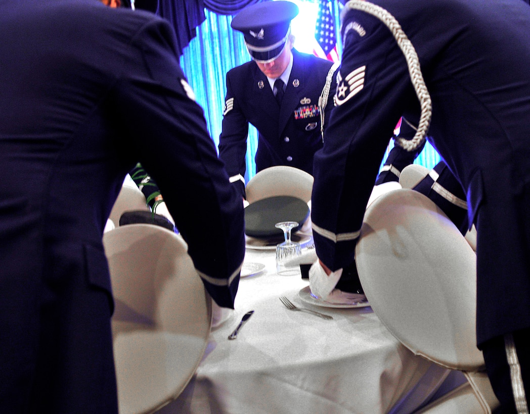 Ramstein honor guard members place a hat for each branch of service on the prisoner of war/missing in action table during a luncheon Sept. 17, 2010, at Ramstein Air Base, Germany. (U.S. Air Force photo/Senior Airman Amanda Dick)