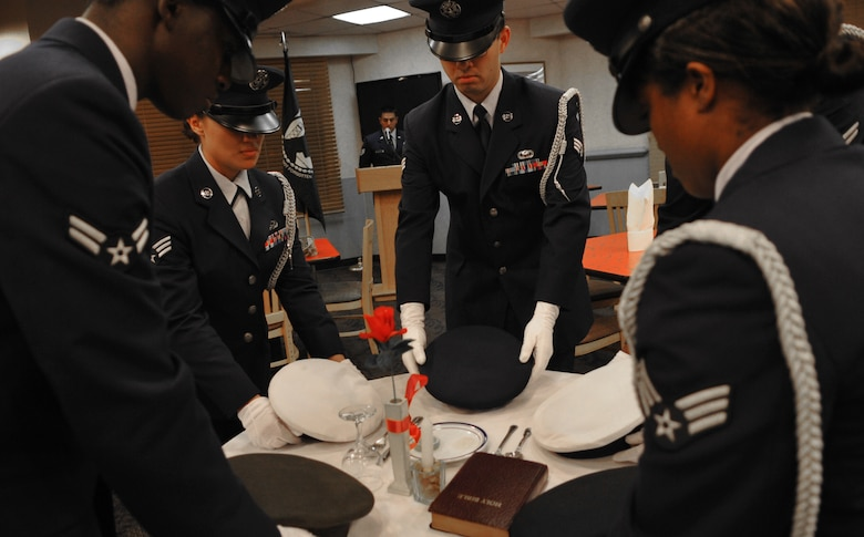Honor guard members set the POW/MIA remembrance table at the Ginko DiningFacility Sept. 16. National POW/MIA Recognition Day is annually observed inthe United States on the third Friday of September. The base heldobservances and ceremonies for the entire week leading up to the nationalobservance. (U.S. Air Force Photo/Senior Airman Evelyn Chavez)