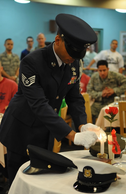 An honor guard member lights a candle at the POW/MIA remembrance table atthe Ginko Dining Facility Sept. 16. National POW/MIA Recognition Day isannually observed in the United States on the third Friday of September. Thebase held observances and ceremonies for the entire week leading up to thenational observance. (U.S. Air Force Photo/Senior Airman Evelyn Chavez)