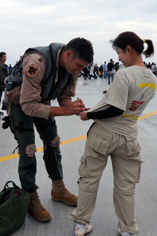 An F-16 Fighting Falcon pilot from the 13th Fighter Squadron autographs a fan's T-shirt at the Misawa Air Festival Sept. 19, 2010, at Misawa Air Base, Japan. (U.S. Air Force photo/Tech. Sgt. Kelly White)