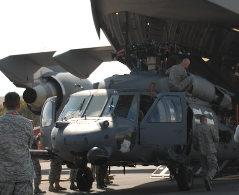 Members of the 106th Rescue Wing from Francis S. Gabreski Air National Guard Base, Westhampton Beach, N.Y., unload an HH-60 Pavehawk from a C-17 Globemaster III at Ysterplaat at Air Force Base, South Africa, for the Africa Aerospace & Defence 2010 exhibition. The New York National Guard participates in a State Partnership Program with the South African National Defence Force and sent an Army National Guard OH-58 Kiowa Scout Helicopter and the Pavehawk rescue helicopter to participate in the exhibition. The C-17 Globemaster III is assigned to a Heavy Airlift Wing from Papa Air Base, Hungary, and routinely supports European Union, NATO and U.N. missions with a strategic airlift and global reach capability. The event runs from Sept. 21-25 (Photo by U.S. Army Staff Sgt. Inman Frank)