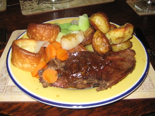 The Sunday roast dinner is still a tradition in many British families, when they all sit down together to eat a veritable feast of roasted meat served with roast potatoes, vegetables and all the trimmings.The more popular roasts are often served with traditional accompaniments. Roast beef is generally served with Yorkshire pudding and horseradish sauce or English mustard as relishes. Roast pork is served with crackling (the crispy skin of the pork), stuffing, apple sauce and English mustard. You should eat your roast lamb with mint sauce and roast chicken with stuffing and bread sauce. There are regional variations to all of these.  Any self-respecting Sunday roast should also be accompanied by gravy made from the meat juices. (U.S. Air Force photo by Suzanne Harper)