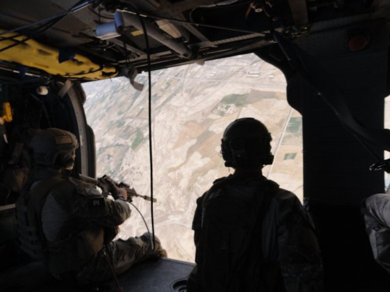 Staff Sgt. Vincent Hnat, a 'Pedro' gunner aboard HH-60G helicopters, keeps a keen eye below during a mission over Southern Afghanistan. Sergeant Hnat said Royal Air Force Regiment medics are zealots when it comes to saving lives, and that as an American, it's great to see a true ally and friend in the fight. (Courtesy photo)