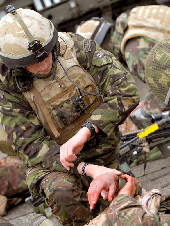 A 51 Squadron Royal Air Force Regiment combat medic from RAF Honington, Norfolk, England, checks a 'wounded' soldier's pulse during an exercise combat scenario. RAF Sgt. Chris Perrio-Stone, 15 Squadron combat medic trainer, crusaded for new and more-realistic training for his medics. As a result, all infantry medics now spend time in United Kingdom hospitals where they are exposed to human blood and real-life smells.  (Royal Air Force Photo)