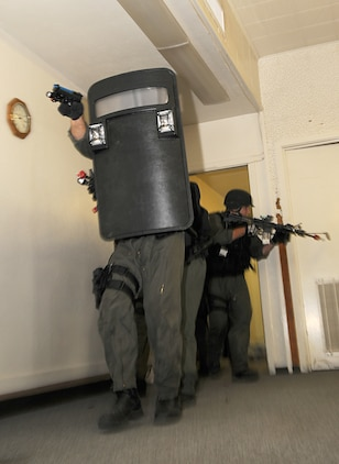 Members of the station's military police special response team move through the halls of the headquarters building during Exercise Desert Fire, Sept. 21, 2010. The exercise was designed to assess the station's response to a workplace shooting. The team made its way through the building before coming into the contact with the shooter, who had taken several hostages in the building.