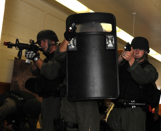 Military police special response team members at the Marine Corps Air Station in Yuma, Ariz., move through the hallways of the station's headquarters building and sight in on a role-playing shooter who had taken several hostages in the building during Exercise Desert Fire, Sept. 21, 2010. The exercise was designed to assess the station's response to an active shooter situation.