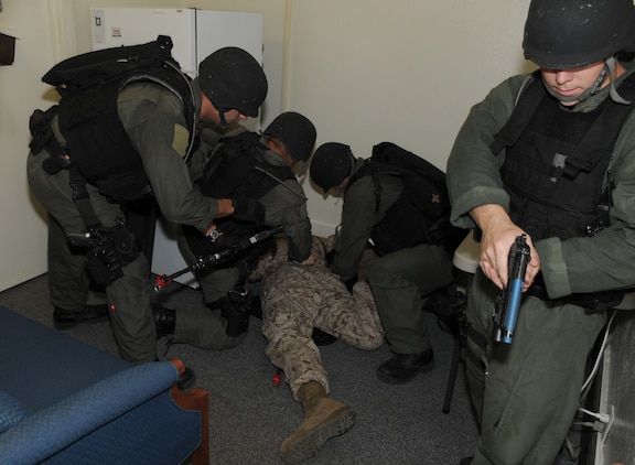 Members of the military police special response team at the Marine Corps Air Station in Yuma, Ariz., take custody of Cpl. David Reames, station armorer, during Exercise Desert Fire, Sept. 21, 2010. During the exercise, Reames played the role of an active shooter in the station's headquarters building before taking hostages and engaging SRT in a shootout. The exercise was designed to assess the station's response to an active shooter situation.