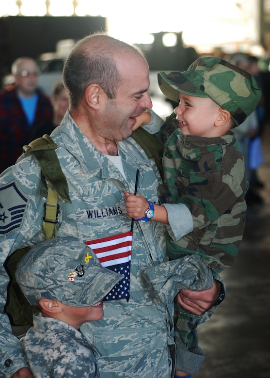 Master Sgt. Thomas Williams, 58th Aerial Port Squadron, sees his sons for the first time in four months.  Sergeant Williams returned from his deployment to Kandahar Airfield Sept. 21 and was greeted by family, friends and fellow Airmen at the Aerial Port Hangar.