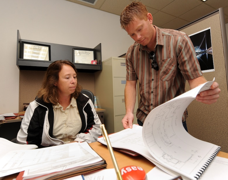 MOUNTAIN HOME AIR FORCE BASE, Idaho -- Connie Gordon, 366th Contracting Squadron architect and engineer contract specialist, reviews building plans with Jason Darst, 366th Civil Engineer Squadron, as the CONS works to complete end of year contracts Sept 10. The Contracting Squadron provides business advice and an overall base acquisition program to support the 366th Fighter Wing's contracting needs. (U.S. Air Force photo by Senior Airman Debbie Lockhart)