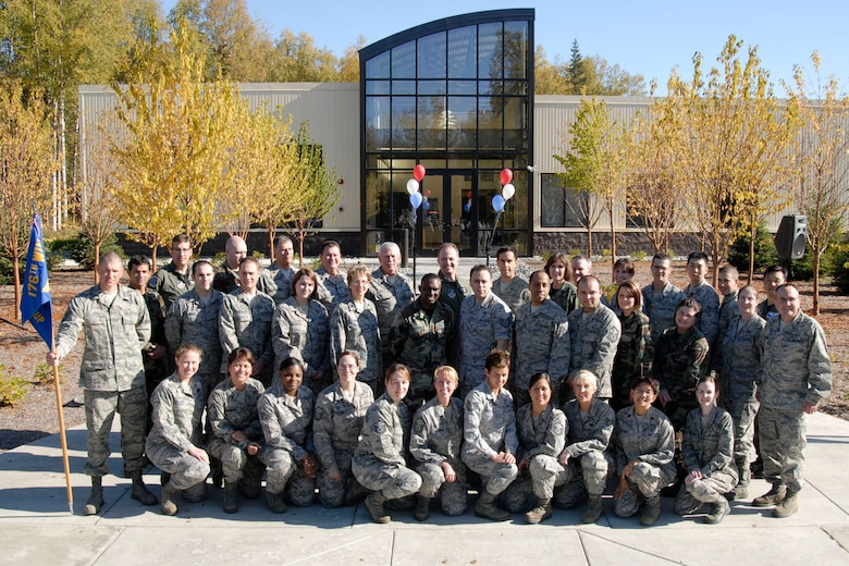 JOINT BASE ELMENDORF RICHARDSON, Alaska -- Members of the 176th Medical Group, Alaska Air National Guard, pose during the ribbon-cutting ceremony for their new Medical Readiness and Training Center here Sept. 19, 2010.  The Medical Group was one the first units from the 176th Wing to relocate here from Kulis Air National Guard Base. All wing units will eventually relocate here as part of the Federal 2005 Base Realignment and Closure (BRAC) legislation; most of the remaining units will make the move in early 2011. Alaska Air National Guard photo by Master Sgt. Shannon Oleson.