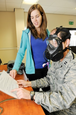 ROYAL AIR FORCE LAKENHEATH, England -- Keisha Faw, 48th Aerospace Medicine Squadron gas mask fit tester, directs Capt. Tony Kasallis, 48th Dental Squadron general dentist, on different exercises to perform when fitting for a gas mask at the deployment center Sept. 22.  A series of five different exercises lasting 40 seconds each, are done to make sure each mask is fitted properly. (U.S. Air Force photo/Airman 1st Class Lausanne Morgan)