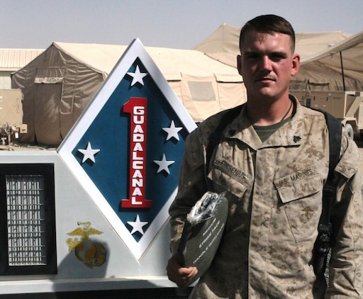 "Sergeant David Fresenius, an assistant team leader with 3rd Platoon, Company B, 1st Reconnaissance Battalion, holds the protective Sapi plate that saved his life, in front of the 1st Marine Division (Forward) Memorial monument, Sept. 24. The 23-year-old from Westminster, Calif., was hit in the top of his back's plate during a small arms fire engagement in Trek Nawa, on June 21, 2010.  The round lodged in his protective gear, just millimeters away from hitting his upper spine.  After his corpsman attended to the wound, that left a baseball-sized welt in his upper back, a very lucky and determined Fresenius re-donned his gear, and got back in the engagement with the Taliban that lasted just over an hour. ""It felt like I had been hit with a sledge hammer,"" Fresenius said.  ""Once I realized I was okay, my only thoughts were to get back to the fight – to get back with my men."""