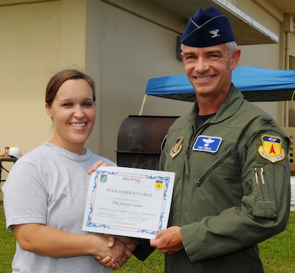 Col. Tod Fingal, 36th Wing vice commander, presents Tech. Sgt. Andrea Inmon, 36th Mobility Response Squadron NCO-in-charge of training, with a certificate after being awarded Andersen's Best at the 36th MRS, Sept. 27. Sergeant Inmon was recognized by her squadron and wing leadership for her innovative process to manually transfer hard copy training records over to Training Business Area, --the Air Forces computerized on the job training records system. (U.S. Air Force photo/ Senior Airman Nichelle Anderson)