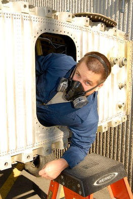 KULIS AIR NATIONAL GUARD BASE, Alaska ? Senior Airman David Eggleston, an aircraft fuels technician, from the 176th Maintenance Squadron exits a training, C-130 integral fuel tank Sept. 19, 2010. The technicians work in two-member teams with one person inside the tank and another on the outside to hand and trade tools and to provide safety back-up for the person on the inside. During an eight-hour day, technician can work up to four hours inside the tank and it can take a week?s worth of time to complete a repair. Alaska Air National Guard photo by Master Sgt. Shannon Oleson.