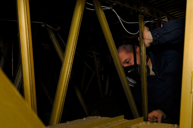 KULIS AIR NATIONAL GUARD BASE, Alaska ? Senior Airman David Eggleston, an aircraft fuels technician, from the 176th Maintenance Squadron crawls inside a training, C-130 integral fuel tank on Sept. 19, 2010. The technicians work in two-member teams with one person inside the tank and another on the outside to hand and trade tools and to provide safety back-up for the person on the inside. During an eight-hour day, technician can work up to four hours inside the tank and it can take a week?s worth of time to complete a repair. Alaska Air National Guard photo by Master Sgt. Shannon Oleson.
