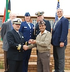 The DIMO team leader CDR Jose Gonzalez presented Lt Kommal a coin for his excellent support.  Lt Kommal liaised between the South African School for Military Health Training and the DIMO team to ensure the training mission went smoothly; Pretoria South Africa, November 2009.  (US Air Force Photo) (US Air Force Photo)