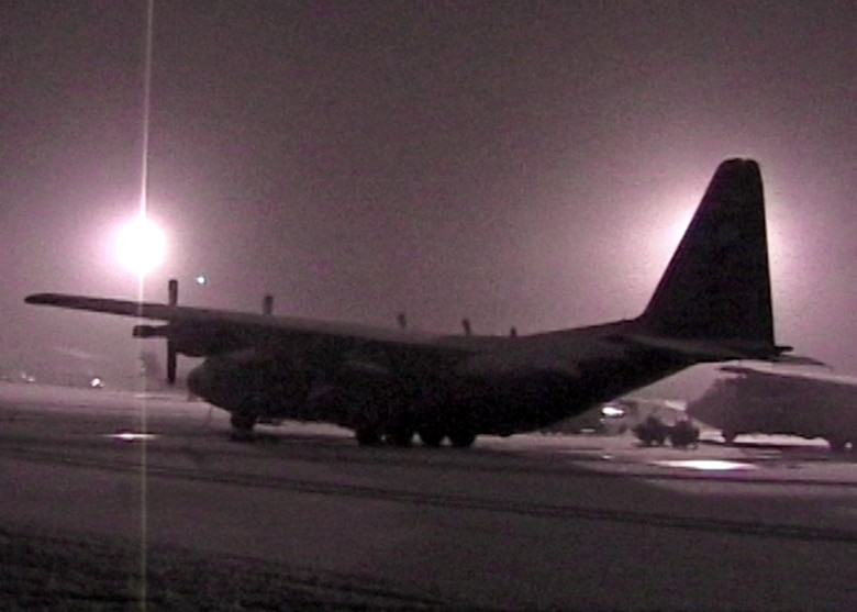 A snow-covered C-130 sits on the ramp at Bagram Air Base, Afghanistan, as deployed 711th Special Operations Squadron members of 'Daddy 05' return from a medical evacuation in 2009.  Due to heavy snowstorms and poor visibility, the Duke Field  reservist aircrew had to receive a waiver just to land.  The medical evacuation mission was a success in that all the critically wounded passengers survived after suffering injuries from a suicide bomber.  (Photo still from video source)