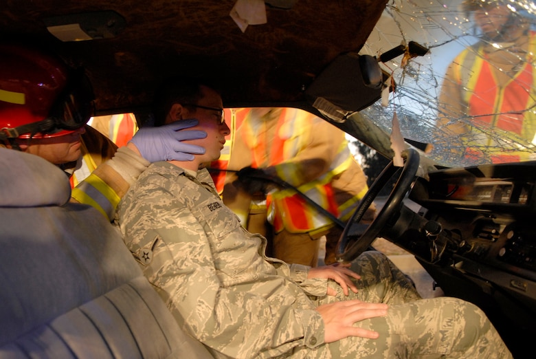 VANDENBERG AIR FORCE BASE, Calif. -- Firefighters of the 30th Civil Engineer Squadron help Airman Gustavo Behrens, a 30th Medical Operations Squadron member, during a simulated car crash here Monday, Sept. 27, 2010. The scenario portrayed is in response to recent accidents involving personnel who were texting while driving. (U.S. Air Force photo/Senior Airman Andrew Satran)