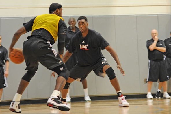 NBA player LeBron James (left) prepares to take the basketball around the defense of teammate Mickell Gladness during a preseason practice session Sept. 28, 2010, at the Aderholt Fitness Center at Hurlburt Field, Fla. The Miami Heat used the fitness center for their week-long training camp. James is a forward and Gladness is a center for the Heat. (U.S. Air Force photo/Senior Airman Sheila deVera)