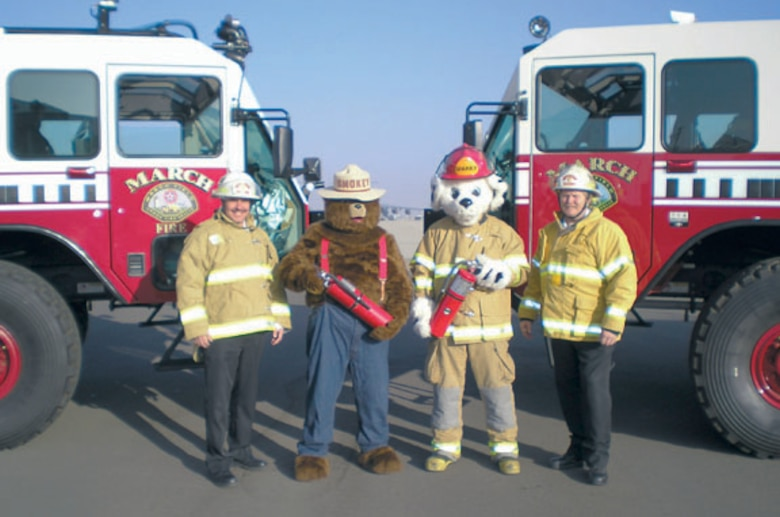 March Fire Chief Jeffrey Konersman (right) and Assistant Chief of Prevention Harold Sterne (left), prepare for Fire Prevention week by posing for a photo with Smokey, Sparky and two fire engines at the March Air Reserve Base Fire Department, Sept. 27, 2010.  (U.S. Air Force photo/ Timothy Williams)