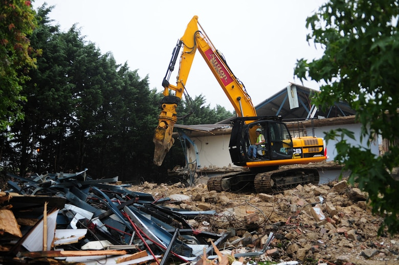 RAF MILDENHALL, England -- Digger driver Rob Saunders, a local contractor, swings his JCB around to drop and pick up old pieces from the wreck of dormitory 212, currently being demolished. The quality of the Airmen's quarters had deteriorated and had become surplus to requirements. Once demolition is complete, which is scheduled for January 2011, the area will be landscaped. (U.S. Air Force photo/Karen Abeyasekere)