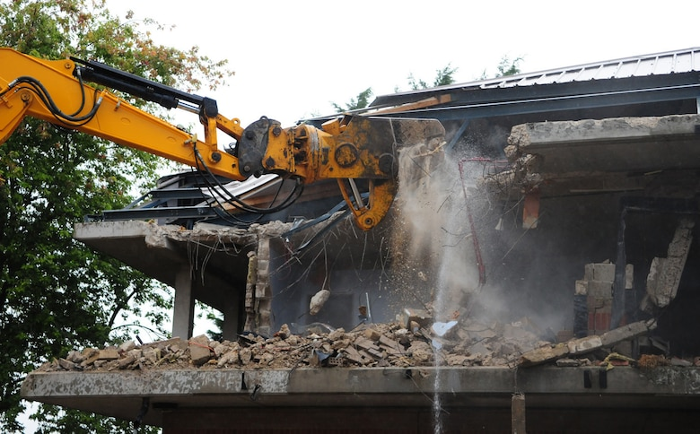 RAF MILDENHALL, England -- Like a dinosaur munching down food, a mechanical digger rips apart Dorm 212 as part of an ongoing demolition project. The quality of the Airmen's quarters had deteriorated and had become surplus to requirements. Once demolition is complete, which is scheduled for January 2011, the area will be landscaped. (U.S. Air Force photo/Karen Abeyasekere)